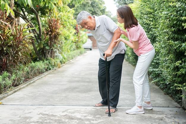 Азиатский пожилой мужчина ходит на заднем дворе и болезненное воспаление и жесткость суставов Premium Фотографии