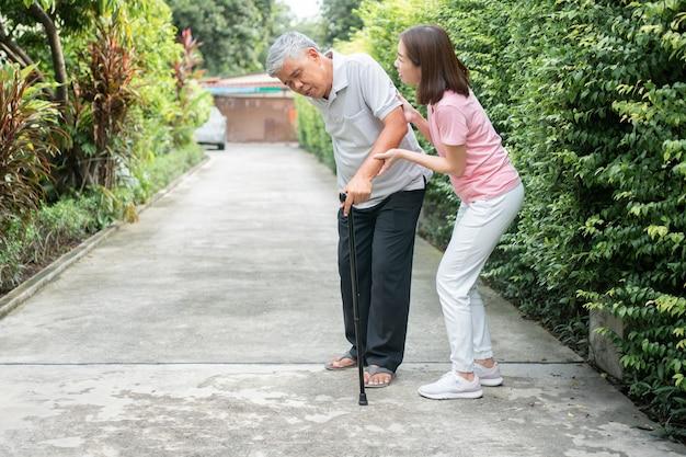 Азиатский пожилой мужчина, идущий на заднем дворе, и болезненная скованность суставов, и дочь пришли помочь поддержать. Premium Фотографии