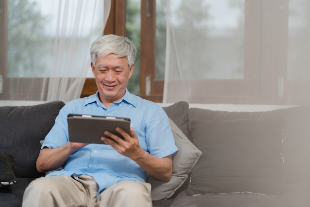 Asian senior men using tablet at home. asian senior chinese male search information about how to good health on internet while lying on sofa in living room at home concept. Free Photo