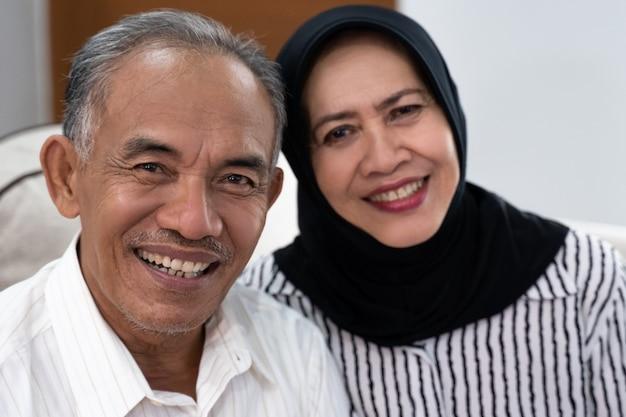 カメラを見てアジアシニアイスラム教徒のカップル Premium写真