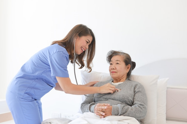 Asian senior old woman on the bed with doctor and her son in hospital Premium Photo