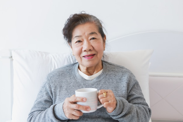 Asian senior old woman drinking coffee or tea on the bed Premium Photo