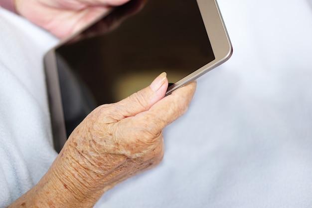 アジアのシニアまたは高齢の老婦人女性は、青い布でタブレットを使用または遊んでいます。ヘルスケア、医療、技術の概念。 Premium写真