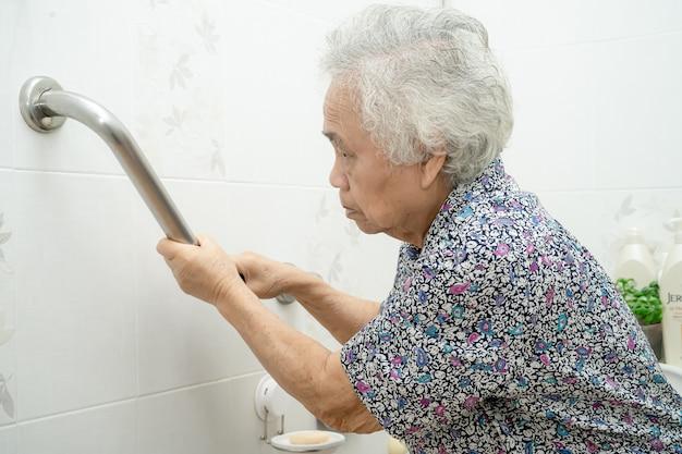 アジアの高齢者または高齢の老婦人女性患者が看護病棟のトイレバスルームハンドルセキュリティを使用 Premium写真