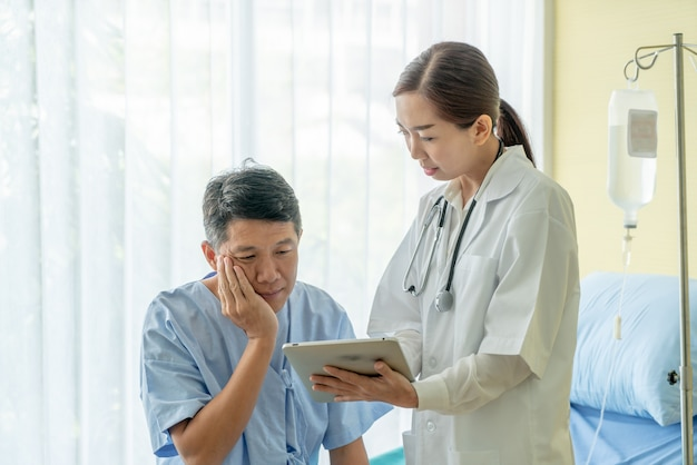 Asian senior patient on hospital bed discussing with female doctor Premium Photo