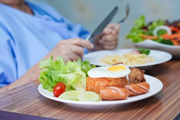 Asian senior woman patient eating breakfast in hospital. Premium Photo