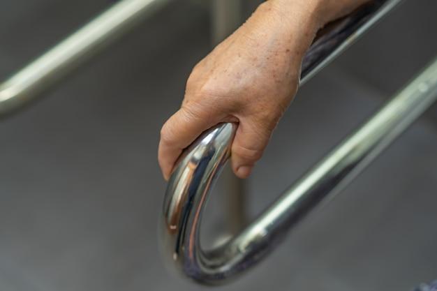 アジアの年配の女性患者は病院でトイレのバスルームハンドルセキュリティを使用します。 Premium写真