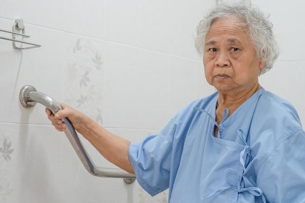 アジアの年配の女性患者はトイレの浴室のハンドルのセキュリティを使用します。 Premium写真