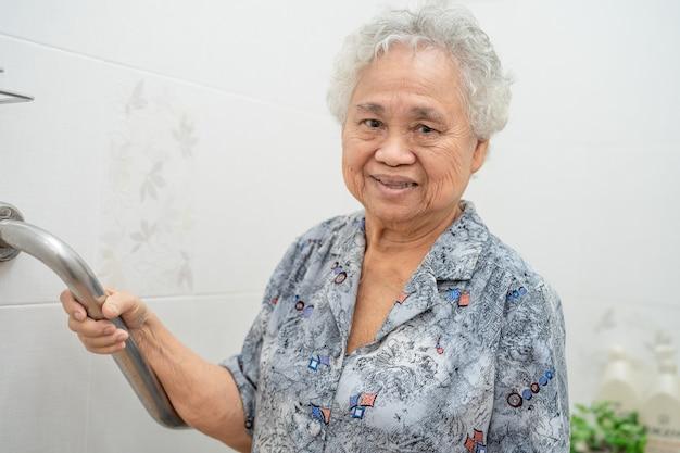 アジアの年配の女性患者はトイレのバスルームハンドルのセキュリティを使用します。 Premium写真