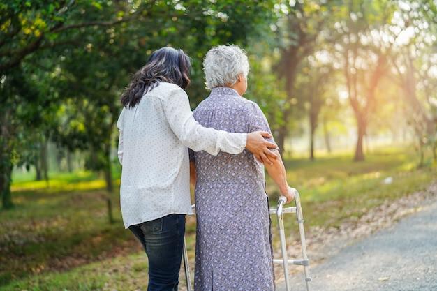 Azjatycka starsza kobieta używa walker w parku.  Zdjęcie Premium