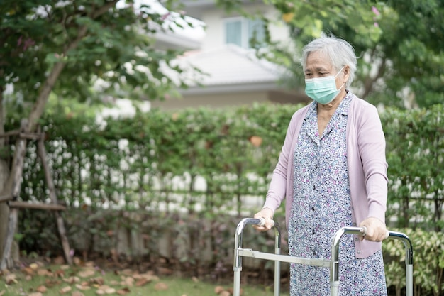 아시아 노인 여성이 워커와 함께 산책하고 코 비드 코로나 바이러스를 보호하기 위해 얼굴 마스크를 착용 프리미엄 사진