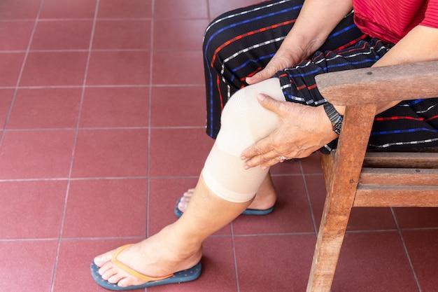 Asian senior woman with bandage compression knee brace support injury. Premium Photo