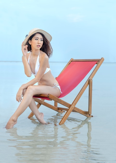 Asian sexy girl with hat and bikini sitting on the beach chair at seaside Premium Photo