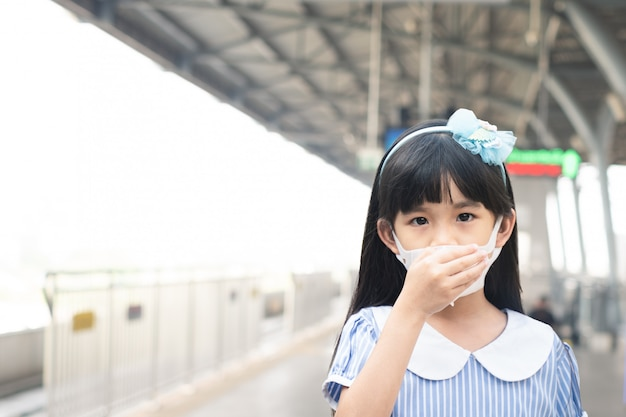 Asian small young girl kid wearing mask for prevent covid-19 or coronavirus infection at train station. Premium Photo