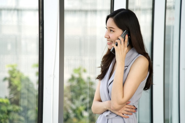 Asian smart beautiful girl talking business on mobile phone ...