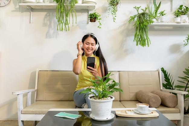 Asian smiling girl student wear wireless headphone study online with skype teacher in a coffee shop Premium Photo
