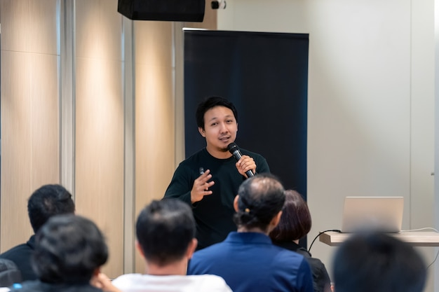 Asian speaker with casual suit on the stage in front of the room with low light Premium Photo