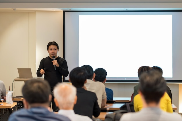Asian speaker with casual suit on the stage in low light Premium Photo