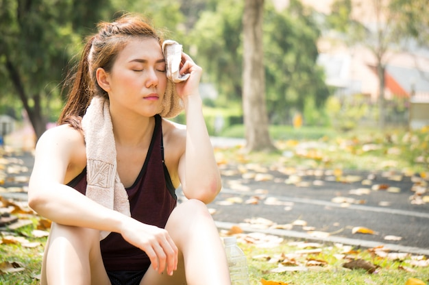 Asian sport woman is tried and rest after running in park Premium Photo