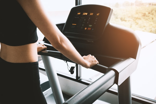 Asian sport woman walking or running on treadmill equipment in fitness workout gym Premium Photo