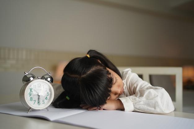 Азиатский студент-ребенок спит, читая книгу в спальне в ночное время Premium Фотографии