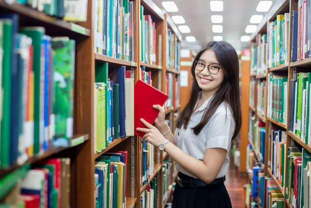 Asian student putting in order books returned after reading Premium Photo