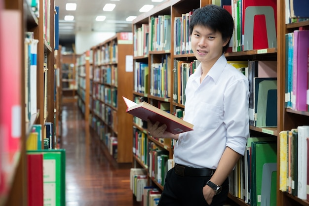 Asian student in uniform reading in the library Premium Photo