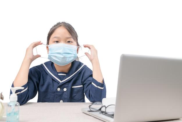 サージカルマスクを着用し、コンピューターで隔離されたeラーニングとcovid-19またはコロナウイルス検疫を研究するアジアの学生。 Premium写真
