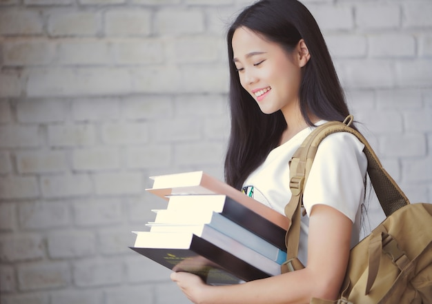 Asian students holding books at university Premium Photo