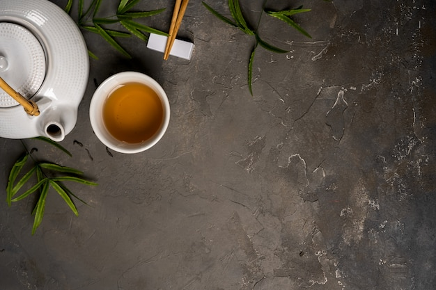 Asian tea concept, cup of tea and teapot surrounded with green tea dry leaves view from above Premium Photo