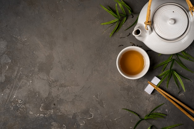 Asian tea concept, cup of tea and teapot with green tea dry leaves view from above, space for a text on dark stone background Premium Photo