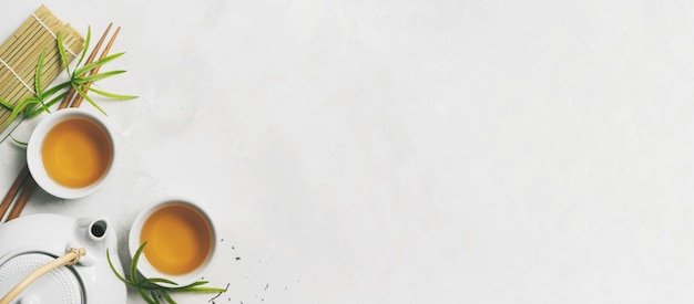 Asian tea concept, two white cups of tea, teapot, tea set, chopsticks, bamboo mat surrounded with dry green tea on white background Premium Photo
