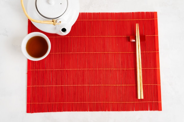 Asian tea food background. teapot and cup with chopsticks on the red bamboo mat over the gray stone background. mockup for the menu. Premium Photo