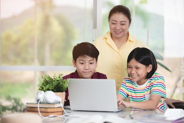 Asian teacher and kids entertaining using laptop computer. Premium Photo