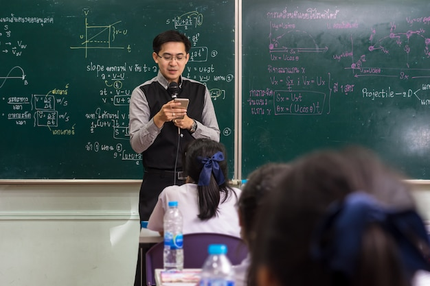 Asian teacher using the smart mobile phone for giving lesson over the the physics formula Premium Photo
