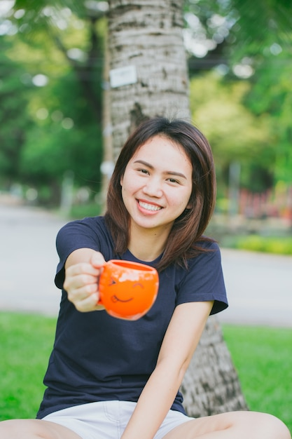Asian teen handle smile mug in the green park. happy drink coffee concept. Premium Photo
