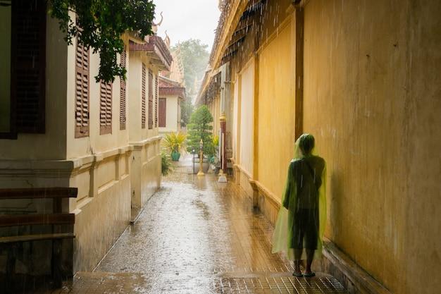 Азиатский подросток ждет муссонный дождь, чтобы остановить. Бесплатные Фотографии