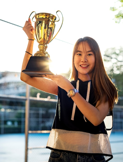 Asian teenage girl in sporty clothes holding up a trophy outdoors Free Photo