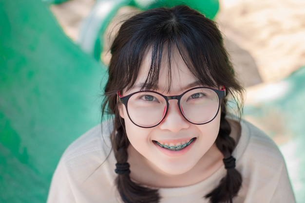 b6deb1af89ad Asian teenage girls wearing glasses and braces are enjoying in the colorful  playground Premium Photo