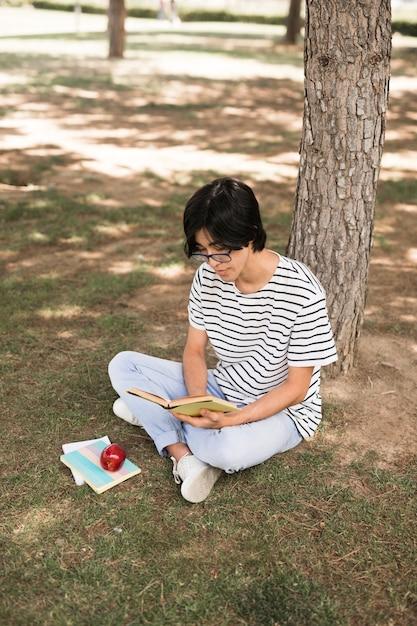 Asian teenage student reading book under tree Free Photo