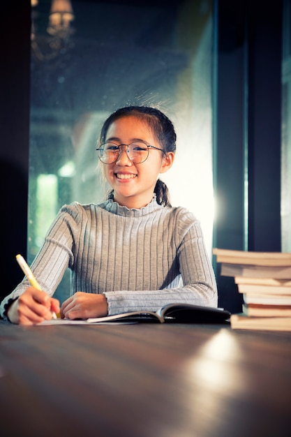 Asian teenager doing school home work in library room Premium Photo