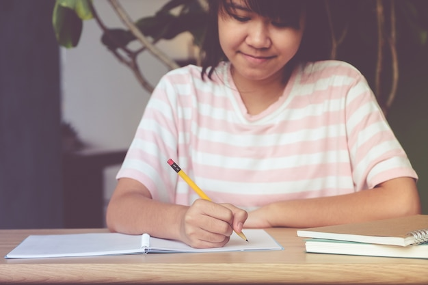 Asian teenager girl student, with smiling face, writing notebook paper on table in her classroom, education concept Premium Photo