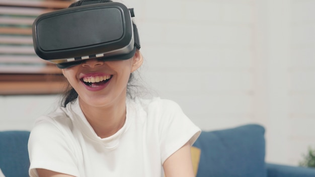Asian teenager woman using glasses virtual reality simulator playing video games in living room Free Photo