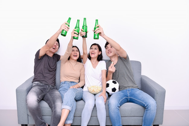 Asian teenagers watching football on television Premium Photo