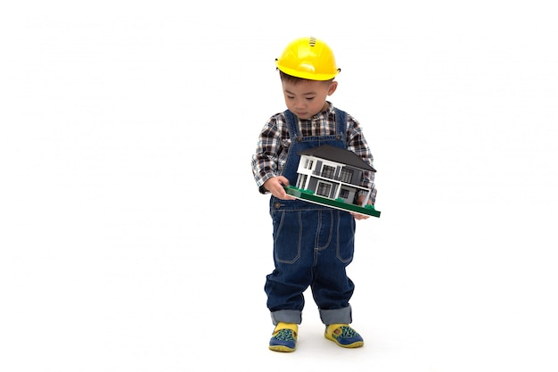 Asian thai baby boy wearing an engineer suit with hard hat and holding a sample house isolated, construction worker Premium Photo