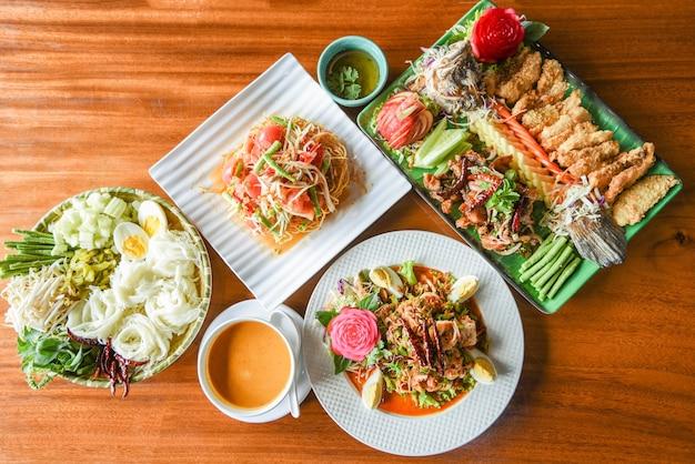 タイのライスヌードルカレーパパイヤサラダ、エビのサラダ、サラダ魚料理とアジアのタイ料理トップビュー木製テーブルの設定プレートで提供しています Premium写真