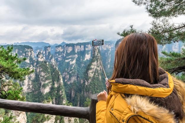 Азиатская туристическая девушка фотографировать с помощью смартфона чжанцзяцзе wulingyuan чанша китай Premium Фотографии