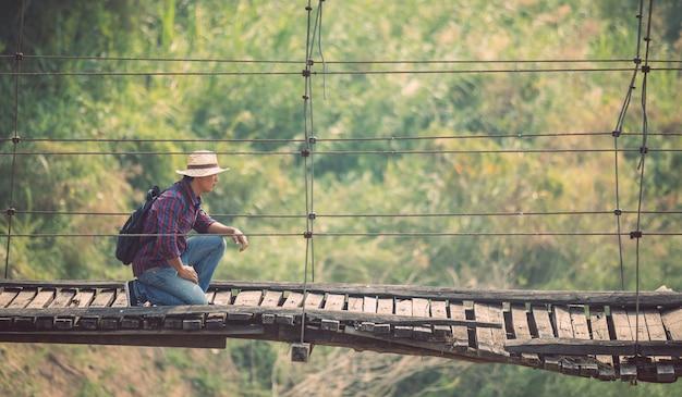 Asian tourist man walking on the old and broken wood bridge Premium Photo