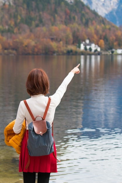 Asian tourist traveller girl standing pointing finger at lake feeling freedom peaceful Premium Photo