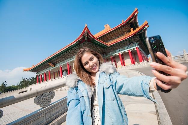 Азиатская туристическая женщина selfing с ее умным телефоном в ориентире тайбэя Premium Фотографии